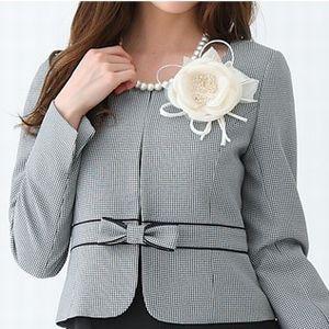 ベーシックなスーツスタイルに華やかなかわいらしさをプラス